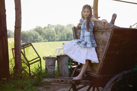 Portrait barefoot girl in dress leaning on rural wagonの写真素材 [FYI04323801]