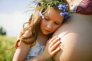 Serene girl with flowers in hair leaning on pregnant mothers stomachの写真素材 [FYI04323802]