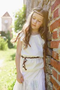 Serene girl in dress leaning against brick wallの写真素材 [FYI04323804]