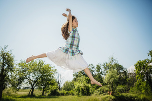 Carefree girl in dress jumping for joy in sunny backyardの写真素材 [FYI04323806]