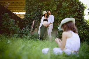Pregnant couple watching daughter sitting in grassの写真素材 [FYI04323810]