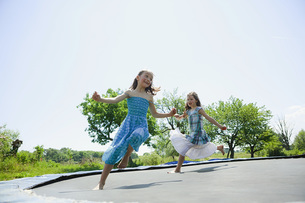 Playful, carefree barefoot girls in dresses playing on trampoline in sunny backyardの写真素材 [FYI04323811]