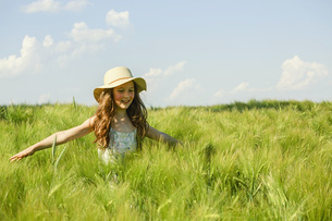 Carefree girl walking in sunny, idyllic green rural fieldの写真素材 [FYI04323812]