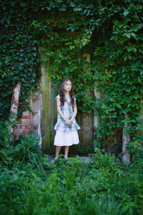 Serene girl in dress standing at rustic door covered with green ivyの写真素材 [FYI04323813]