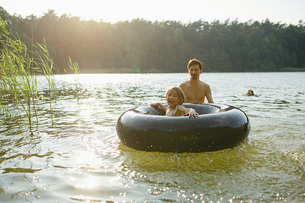 Father and daughter playing with inner tube in sunny summer lakeの写真素材 [FYI04323816]