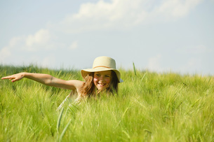 Carefree, happy girl in sunny rural green wheat fieldの写真素材 [FYI04323819]