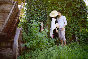 Affectionate pregnant couple standing at ivy covered wallの写真素材 [FYI04323821]