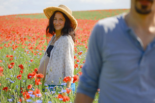 Portrait smiling pregnant woman standing in sunny, rural red poppy fieldの写真素材 [FYI04323823]