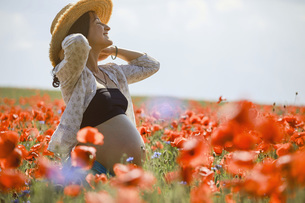 Carefree pregnant woman in sunny, idyllic rural red poppy fieldの写真素材 [FYI04323825]