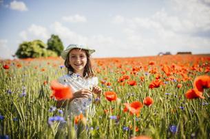 Portrait happy, carefree girl in sunny, idyllic rural red poppy fieldの写真素材 [FYI04323827]