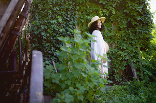 Portrait happy pregnant woman standing at ivy covered doorの写真素材 [FYI04323835]