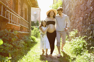 Pregnant family walking along sunny farmhouseの写真素材 [FYI04323838]
