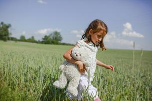 Girl with teddy bear walking in sunny, rural green fieldの写真素材 [FYI04323839]