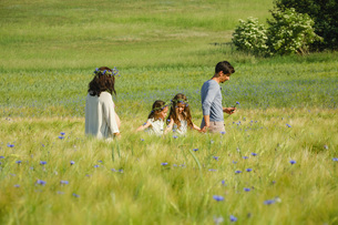 Family walking in sunny, idyllic rural green field with wildflowersの写真素材 [FYI04323840]
