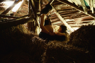 Pregnant mother and daughter in rural hay loftの写真素材 [FYI04323841]