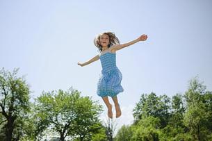 Carefree girl in dress jumping for joy in sunny backyardの写真素材 [FYI04323846]