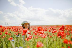 Girl in sunny, idyllic rural red poppy fieldの写真素材 [FYI04323847]