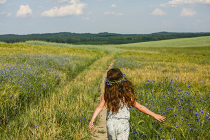 Girl running in sunny, rural idyllic green field with wildflowersの写真素材 [FYI04323848]