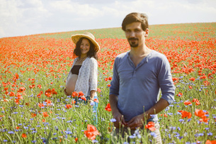 Portrait smiling pregnant couple in sunny, idyllic rural red poppy fieldの写真素材 [FYI04323853]