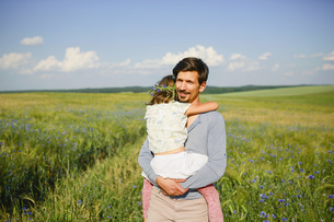 Portrait father holding daughter in sunny, idyllic rural field with wildflowersの写真素材 [FYI04323854]