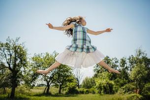 Carefree girl in dress jumping for joy in sunny backyardの写真素材 [FYI04323855]