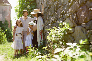 Portrait pregnant family at sunny stone wall in gardenの写真素材 [FYI04323857]