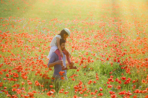 Father carrying daughter on shoulders in sunny idyllic rural field with red poppiesの写真素材 [FYI04323858]