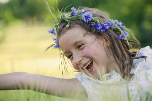 Happy, carefree girl with flowers in hairの写真素材 [FYI04323859]