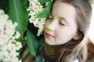 Serene girl leaning against flowerの写真素材 [FYI04323860]