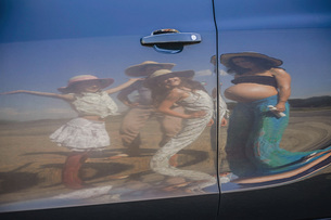 Reflection of pregnant woman and family on sunny car doorの写真素材 [FYI04323861]