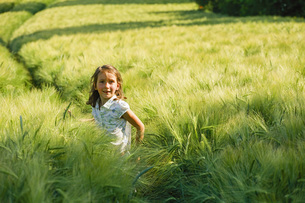 Portrait smiling girl in rural, green wheat fieldの写真素材 [FYI04323863]