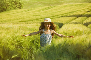 Portrait happy, carefree girl running sunny rural fieldの写真素材 [FYI04323865]