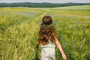 Girl with flowers in hair walking in sunny, idyllic green fieldの写真素材 [FYI04323870]