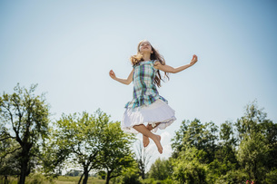 Carefree girl in dress jumping for joy in sunny backyardの写真素材 [FYI04323872]