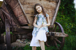 Serene girl in dress with flowers in hair at rural wagonの写真素材 [FYI04323873]