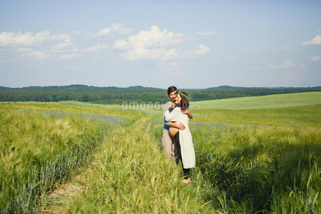 Affectionate pregnant couple hugging in sunny, idyllic rural green fieldの写真素材 [FYI04323875]
