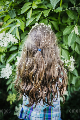 Girl with flowers in hair at blooming bushの写真素材 [FYI04323877]