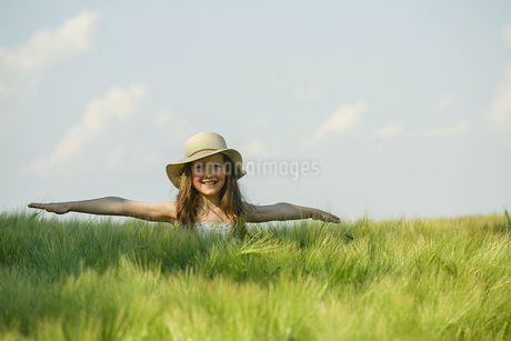Portrait carefree girl with arms outstretched in sunny, rural green fieldの写真素材 [FYI04323878]