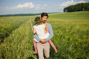 Portrait father carrying daughter in sunny, idyllic rural fieldの写真素材 [FYI04323880]