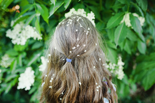 Girl with flowers in hair standing at flowering bushの写真素材 [FYI04323882]