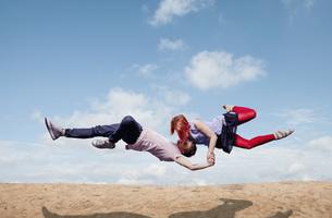Modern aerialist dancers performing, flying over beachの写真素材 [FYI04323883]