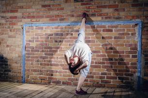Female modern dancer performing against brick wallの写真素材 [FYI04323896]