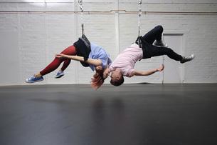 Modern aerialist dancers performing, hanging upside-downの写真素材 [FYI04323899]
