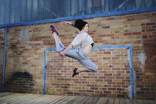 Female modern dancer performing against brick wallの写真素材 [FYI04323903]