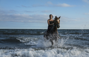 Woman riding horse in ocean surfの写真素材 [FYI04323923]