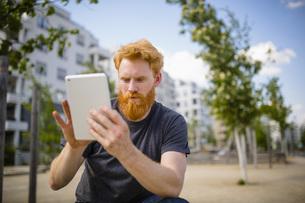 Man with beard using digital tablet in cityの写真素材 [FYI04323962]