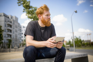 Hipster man with beard using digital tablet on urban benchの写真素材 [FYI04323965]