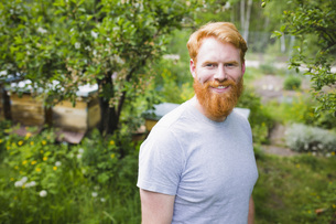 Portrait smiling, confident man with red hair in gardenの写真素材 [FYI04323975]