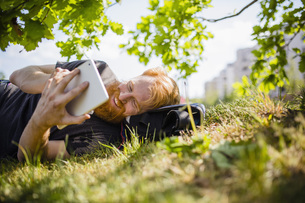 Smiling man with beard using digital tablet in sunny parkの写真素材 [FYI04323977]