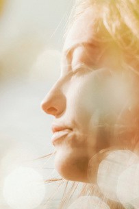Close up profile serene woman basking in sunshineの写真素材 [FYI04323988]